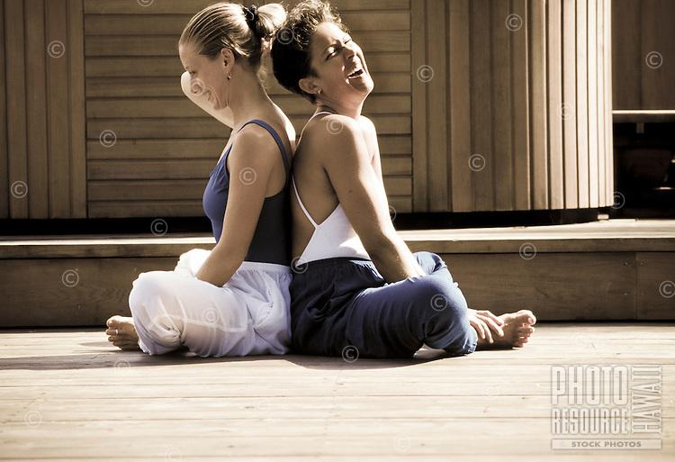 Women practicing parnter yoga