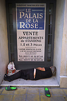 """France. Alpes-Maritimes department. Menton. Town center. Homeless man sleeps in front of an advertising for a real estate company selling new flats at  """" Le Palais de la Rose"""". Dress and phone number are written on the poster. Menton is a commune in the Alpes-Maritimes department in the Provence-Alpes-Côte d'Azur region on the French Riviera. 27.07.2020 © 2020 Didier Ruef"""