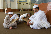 Zliten, Libya. Boys Write Verses from the Koran on their Prayer Boards in the Madrasa of Sidi Abdusalaam.  Their teacher, or muqri, supervises.  He wears the traditional white garment, a juba, and a traditional hat, a tagiyah.