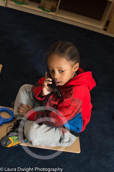 Preschool 3-4 year olds boy sitting by himself talking into telephone pretend play