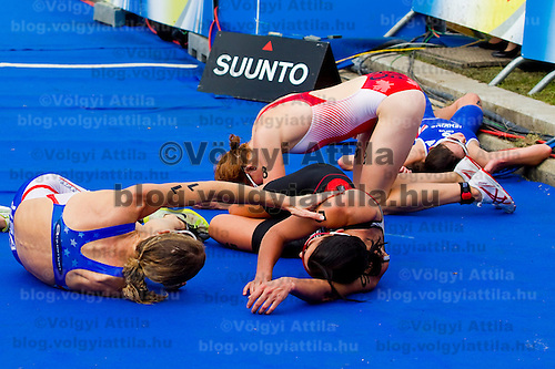 Fully exhausted competitors Laura Bennett (USA left), Nicola Spring (SUI center) and Paula Findlay (CAN right) lie on the ground just after finishing the ITU women's elite triathlon world championships series final in Budapest, Hungary, Sunday, 12. September 2010. ATTILA VOLGYI