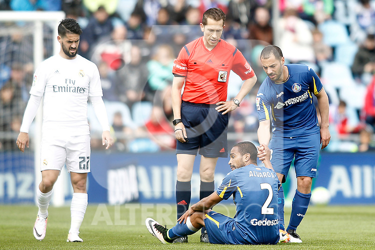 Getafe's Alvaro Pereira injured in presence of Mehdi Lacen (r), Real Madrid's Isco Alarcon (l) and the referee Gonzalez Gonzalez during La Liga match. April 16,2016. (ALTERPHOTOS/Acero)