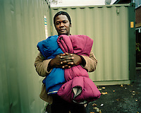 "28 year old Anwar, from the Darfur region of Sudan, collects sleeping bags at a drop-in centre for asylum seekers in North London. He claimed asylum in 2004 after escaping from the ethnic violence in Darfur and spent time destitute, surviving on the kindnss of friends, until 2008 when he was granted leave to remain in the UK. He is overjoyed to be safe but is still struggling to survive and has not managed to find any accommodation. ""I'm sleeping rough and it has caused my feet to swell. My GP is trying to help me get accommodation."".."