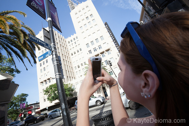 Teen girl taking a picture of the Hollywood and Vine street signs in Hollywood, Los Angeles, CA