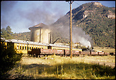 Excursion train passing Hermosa tank with gondolas on siding.<br /> D&amp;RGW  Hermosa ?, CO