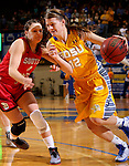 BROOKINGS, SD - FEBRUARY 21:  Macy Miller #12 from South Dakota State drives past Tia Hemiller #4 from the University of South Dakota in the first half of their game Saturday evening at Frost Arena in Brookings. (Photo by Dave Eggen/Inertia)