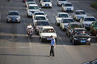 A traffic cop directs cars, buses, taxis, motorcycles and scooters, at a busy intersection in Xian, Shaanxi, China.