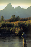 A young man fly fishes at sunset in Grand Teton National Park, Jackson Hole, Wyoming.