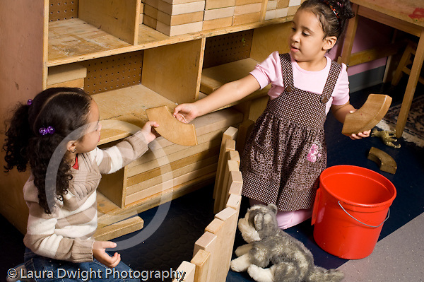Preschool 3-4 year olds two girls building together with wooden blocks in block area one offering the other a block sharing cooperation horizontal