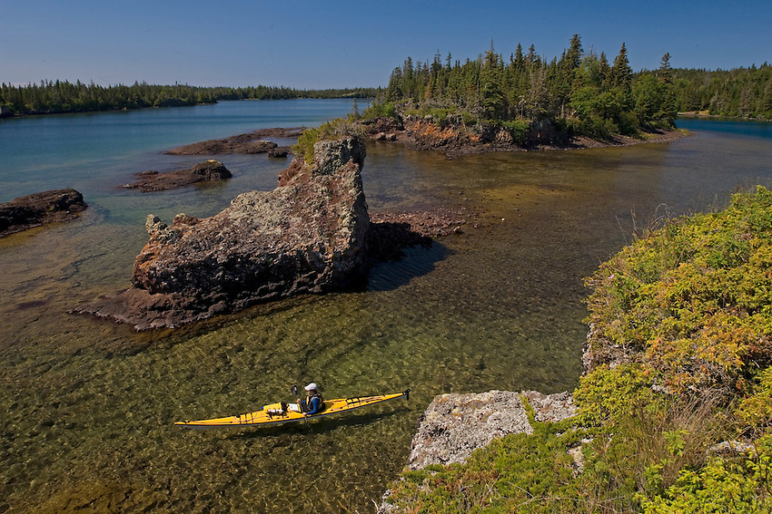 A sea kayaker along the rugged Lake Superior shoreline of Isle Royale National Park Michigan.