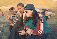 Kosovar Albanian refugees listen to the radio for news at a refugee camp in Macedonia.