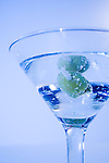 Martini glass with olives in tinted blue background light