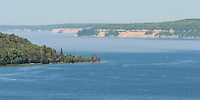 A view of the Grand Island East Channel Lighthouse, Munising Bay and the Pictured Rocks National Lakeshore through a hovering fog. Munising, MI