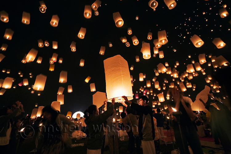 Revellers launch khom loi (sky lanterns) into the night sky during Yi Peng festivities - part of the Loi Krathong festival in Chiang Mai.  San Sai, Chiang Mai province, THAILAND.