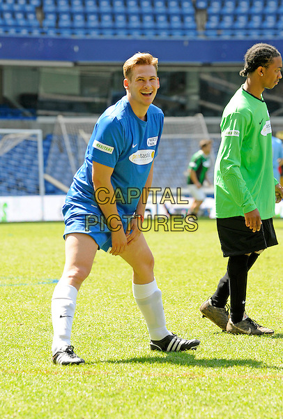 LEE RYAN.Celebrity Soccer Six in aid of The Samaritans held at Chelsea Football ground, Stamford Bridge, London, England..May 24th 2009 .football match game full length white top shorts socks blue bending stretching .CAP/FIN.©Steve Finn/Capital Pictures.