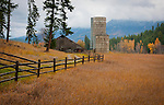 Idaho, North, Bonners Ferry. A barn, fence and rustic silos against the Purcell Mountains in autumn.