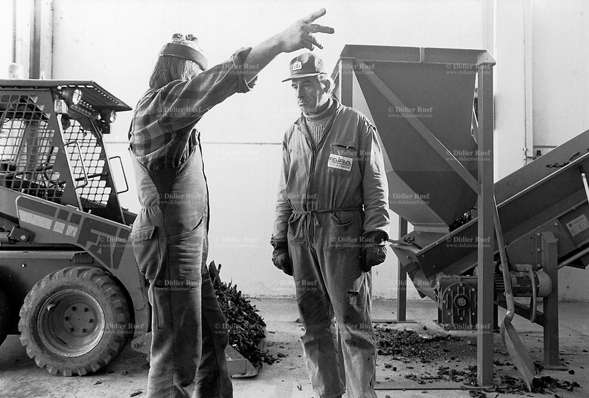 Italy. Bologna Region. Pieve de Cento. Politec (Himont) company.  Cars scrapyard. The polyprophylene bumpers are ground down for recycling. Discussion between two manual workers.  © 1993 Didier Ruef .