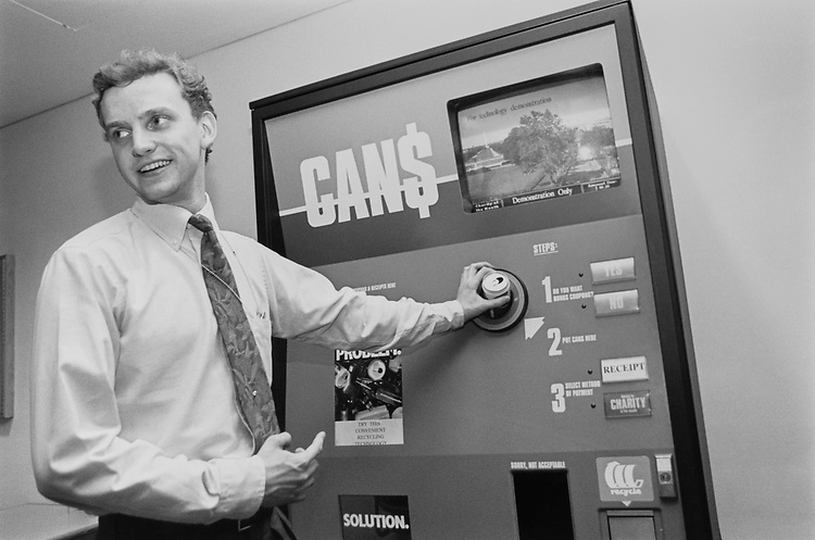 "Brad Rolfs, staff member of Sen. David Durenberger on Environment Affairs, shows a friends how to recycle cans in Dirksen Café at ""Demo Recycling Machine"", on June 10, 1991. (Photo by CQ Roll Call via Getty Images)"