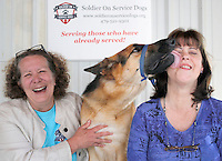 NWA Democrat-Gazette/DAVID GOTTSCHALK  Scout, a one year old service dog in advance training, sneaks in a lick of Elise Burt (right), veterans program manager, while sitting with Angie Pratt, executive director, Thursday, May 19, 2016, at the Soldier On Service Dogs facility in Fayetteville.