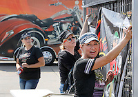 NWA Democrat-Gazette/DAVID GOTTSCHALK  Sheila Schafer (from left), Diana Taylor and Chandra Taylor, owner of 85mph Hats, hang their banner and merchandise Tuesday, September 22, 2015 in the Baum Stadium Parking lot in Fayetteville. The vendors are preparing for the 16th annual motorcycle rally Bikes, Blues and BBQ that runs September 23-26.