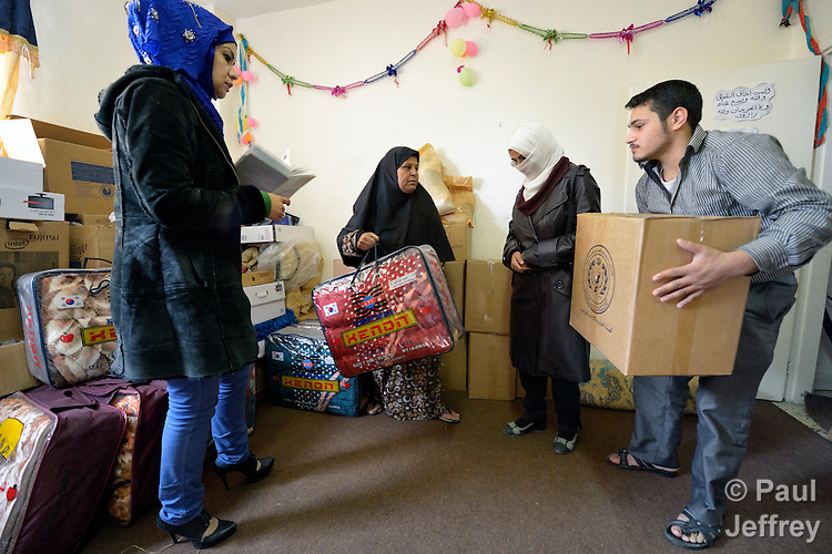 Khawha-Yousuf Al-Hanini (left) is director of Ansan, a local committee that helps refugees in Amman, Jordan. Here she coordinates distribution of relief supplies to Syrian refugee families...