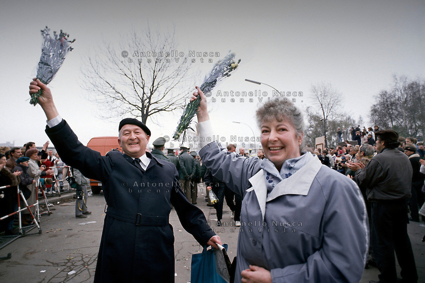 Berlino, 9 Novembre, 1989. Una coppia di Tedeschi dell'Est entra a Berlino Ovest attraverso un varco nel muro subito dopo la sua caduta. East German citizens are applauded by West Berliners as they crossed the border to visit West Berlin. Thousands of East Germans moved into West Berlin after the opening of the wall by East German government.