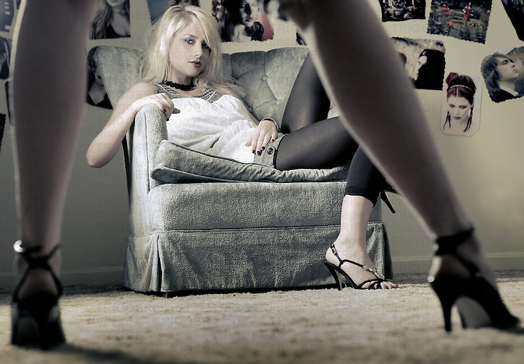 A young woman with blonde hair sitting in an arm chair