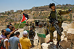 An Israeli soldier threatens members of the press (unseen) with a concussion grenade as they try to report on a demonstration against Israel's controversial separation barrier in the West Bank town of Beit Jala near Bethlehem on 04/07/2010.