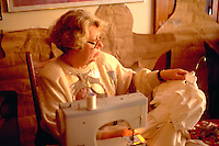 Grandmother age 58 making flower girl wedding dresses.  St Paul  Minnesota USA
