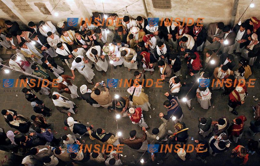 Yemen, Gennaio 2006..San'a, la città vecchia della capitale fatta di vicoli e di suq e' stata dichiarata tra i siti protetti dall'Unesco...Nella foto: Festa di Nozze, ballo tradizionale degli uomini che insieme allo sposo danzano sotto le finestre delle donne nascoste dietro le tende.....Wedding vigil, men dancing under the women windows.........Photo Antonietta Baldassarre Insidefoto(www.insidefoto.com)