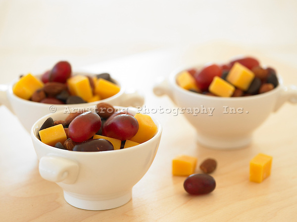Bowls of kids snack/trail mix, with grapes, almonds, and cheddar cheese cubes