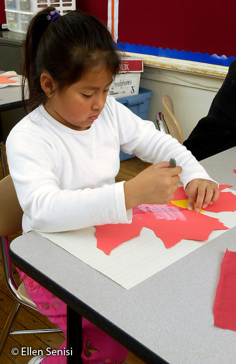 MR / Schenectady, NY .Yates Arts in Education Magnet School, Grade 2.Arts-Themed Urban Elementary School.Student does in-class art project on fall colors using colored tissue paper and paste..Girl: 7, Guatemalan-American, Native American..MR: Thi4.© Ellen B. Senisi