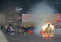 Oct. 6, 2012; Mohnton, PA, USA: NHRA Brandon Bernstein (left) races alongside top fuel dragster driver Spencer Massey who has an engine explosion during qualifying for the Auto Plus Nationals at Maple Grove Raceway. Mandatory Credit: Mark J. Rebilas-