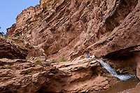 Sitting beside a Sulphur Creek waterfall, a hiker is dwarfed by the Goose Neck Canyons of Capitol Reef National Park.