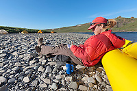 Journalist Molly Loomis takes notes along the Utukok river, National Petroleum Reserve Alaska, Arctic, Alaska.