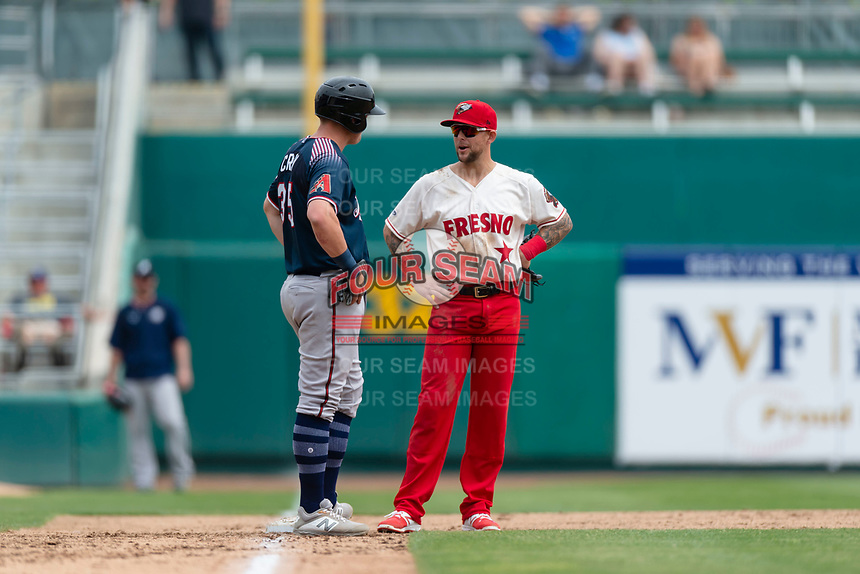 Fresno Grizzlies third baseman Brandon Snyder (10) talks to Kevin Cron (35) during a game against the Reno Aces at Chukchansi Park on April 8, 2019 in Fresno, California. Fresno defeated Reno 7-6. (Zachary Lucy/Four Seam Images)