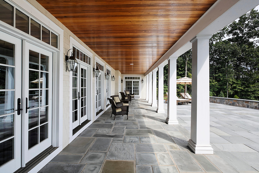 Covered flagstone loggia with columns, wood plank ceiling, French doors,