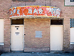 Ruins of now-abandoned brick building with weathered bar and cafe neon signs, doors, all soon to be demolished, Carlin, Nevada