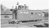 Caboose #0584, 26' long, at Durango.  (With magazine article on D&amp;RGW long caboose.)  Man standing on roof leaning against Cupola.<br /> D&amp;RGW  Durango, CO  Taken by Maxwell, John W. - 6/2/1957