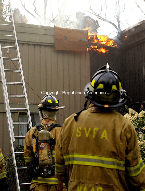 Southbury, CT-18 April 2012-041812CM02- A fire starts back up as Southbury Volunteer Firefighters cut a hole in the roof at a condo complex that caught fire inside Heritage Village Wednesday afternoon in Southbury.   Christopher Massa Republican-American