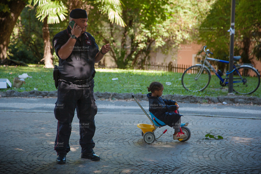 Italy. Lombardy Region. Como. Homeless african migrants living in the park below the San Giovanni railway station. An Italian Carabinieri talking on his mobile phone and and a young Ethiopian child riding a tricycle. The Carabinieri is the national gendarmerie of Italy, policing both military and civilian populations. 11.08.2016 © 2016 Didier Ruef