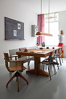 The honey colour of the wooden kitchen table and chairs, combined with the pink curtains, gives the industrial style of this room a warmth