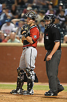 Birmingham Barons catcher Kevan Smith (32) talks with umpire Steve Marcum during a game against the Chattanooga Lookouts on April 24, 2014 at AT&T Field in Chattanooga, Tennessee.  Chattanooga defeated Birmingham 5-4.  (Mike Janes/Four Seam Images)