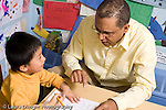 Educaton preschool 4-5 year olds male teacher sitting at table with boy talking about the alphabet letters he is writing horizontal