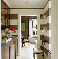 The perspex brackets on the olive-and-white striped walls of the butler's pantry are vintage American and the sculpture which can be seen on the window sill of the dining room beyond is by Donald Baechler