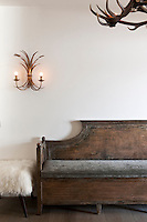 A rustic antique wooden bench is matched with a delicate wall sconce
