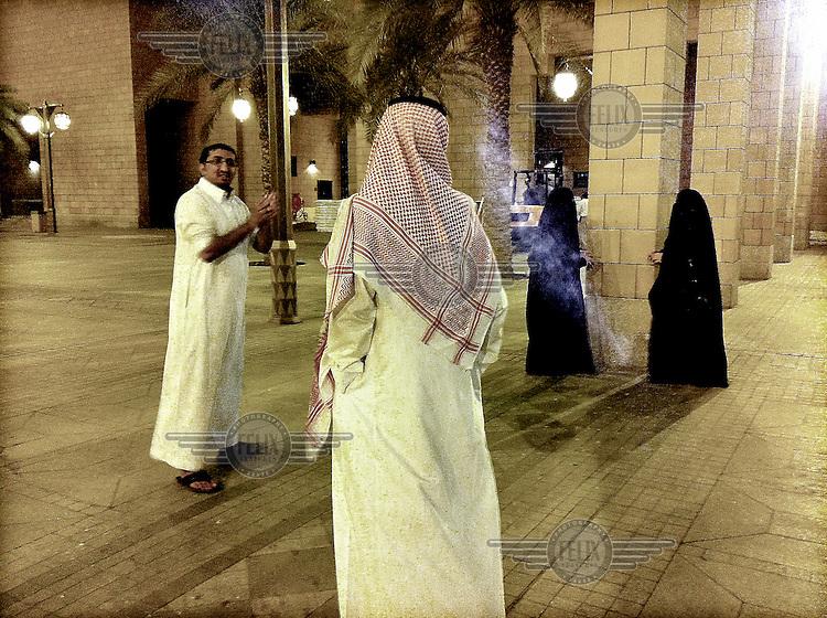 Men and women (standing apart) in Al Safa Square in Al Dirah.