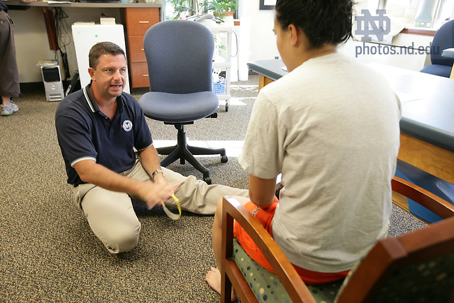 Physical therapist Mike Henderson talks with student Katherine Montalto in the PT room in St. Liam Hall.