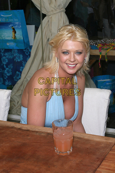 TARA REID .hanging out at Nikki Beach near the sands at the Carlton Hotel: 2006 Cannes International Film Festival, France, day 7.  .May 22nd, 2006.Photo: Zach Lipp/AdMedia/Capital Pictures.Ref: ZL/ADM.half length blue top cleavage table sitting.www.capitalpictures.com.sales@capitalpictures.com.© Capital Pictures.