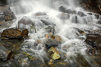 Water cascades on the rocks at the base of an unnamed waterfall in Alaska's Chugach National Forest.